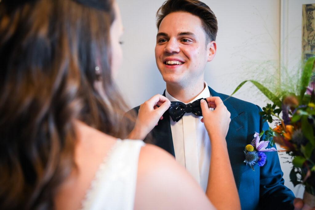 Bruid trekt strik van bruidegom recht bij eerste ontmoeting. Huwelijksfotografie in reportagestijl.