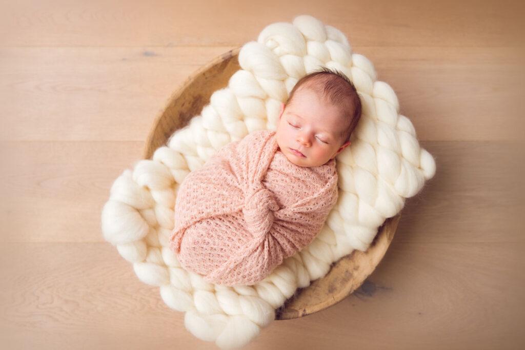 Volledig ingebakerde baby met knoop vooraan liggend in houtenschaal. Babyfotografie
