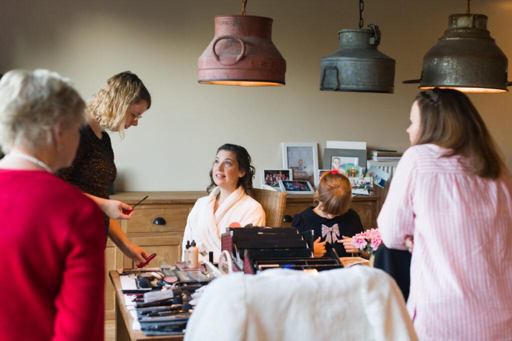 Bruid in voorbereiding op het huwelijk met maquillage. Huwelijksfotografie in reportagestijl