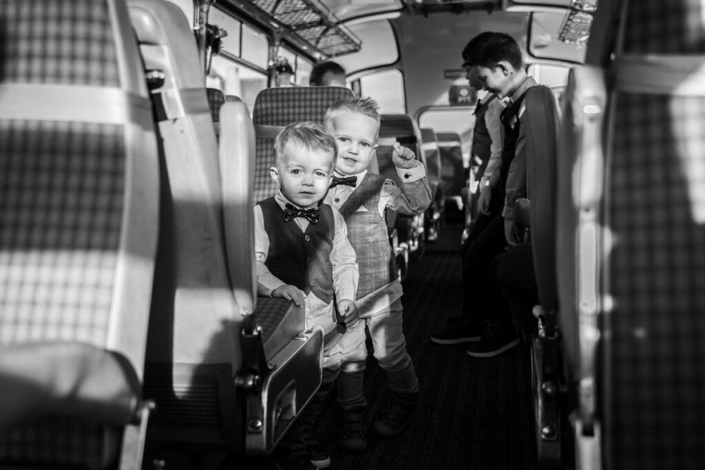 Bruidegom wachtend in bus op de bruid met kinderen en neefjes. Huwelijksfotografie in reportagestijl