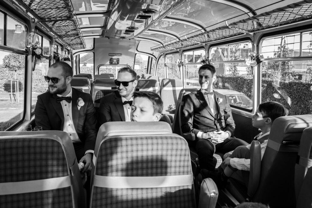 Bruidegom wacht vol spanning in een bus op zijn bruid. Huwelijksfotografie in reportagestijl