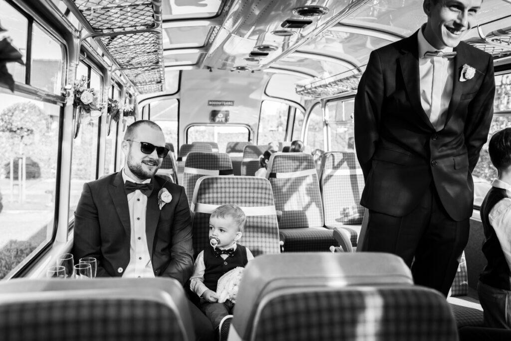 Bruidegom in pak en strik wandelt door de bus wachtend op bruid. Huwelijksfotografie in reportagestijl