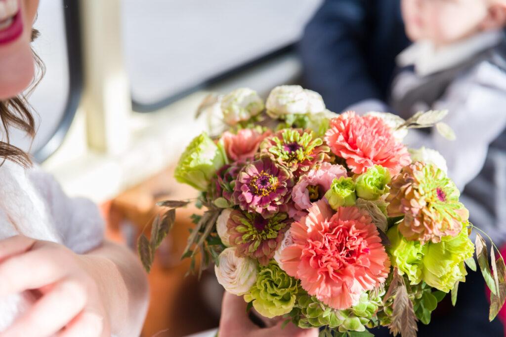 Bruidsboeket met roze en paarse bloemen in close-up. Huwelijksfotografie in reportagestijl
