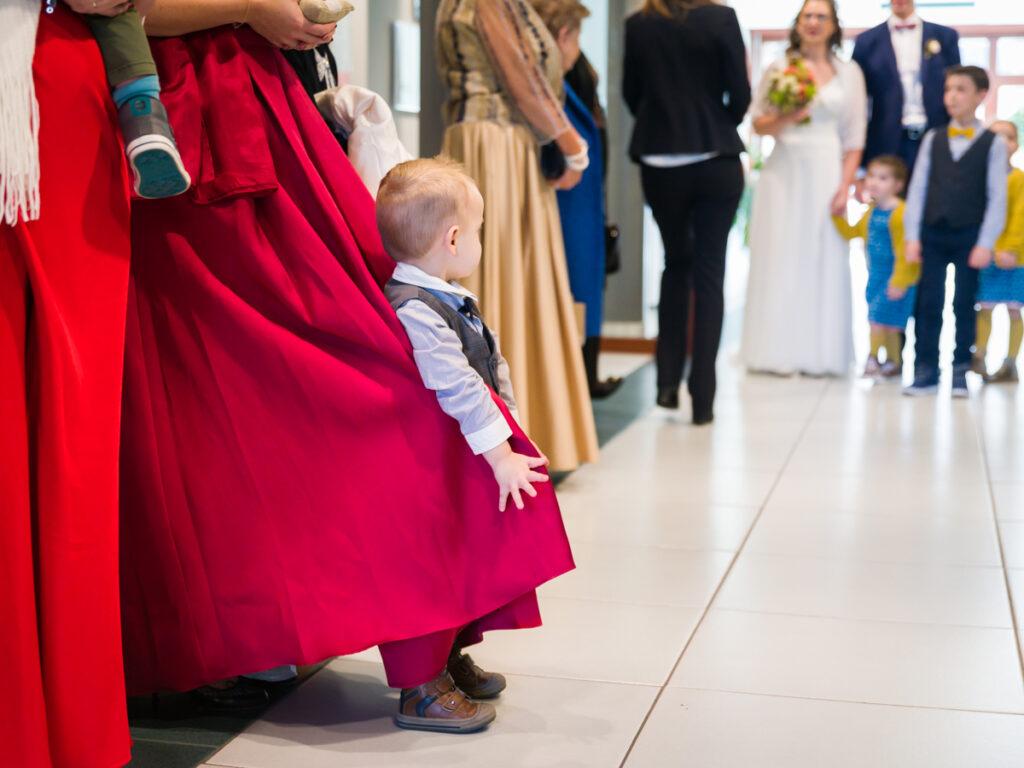 Neefje van het huwelijkspaar die zich in het kleed van zijn mama wikkelt, wachtend in het gemeentehuis. Huwelijksfotografie in reportagestijl