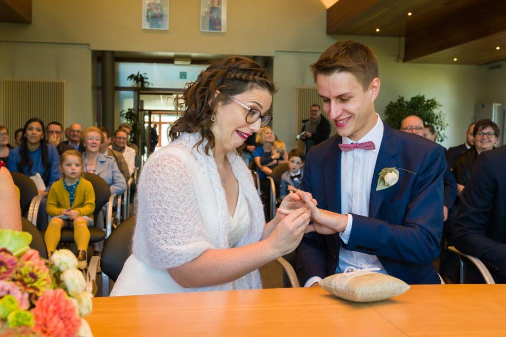 Bruid en bruidegom die elkaar de ringen geven. Huwelijksfotografie in reportagestijl