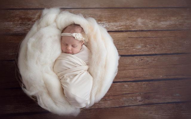 Babyfotografie newborn slapend in witte wrap op houten achtergrond.