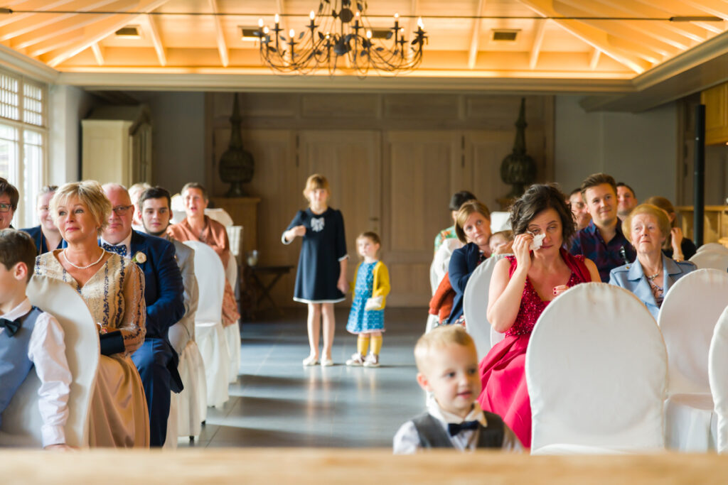 Kinderen hand in hand net voor huwelijksceremonie in feestzaal. Huwelijksfotografie in reportagestijl