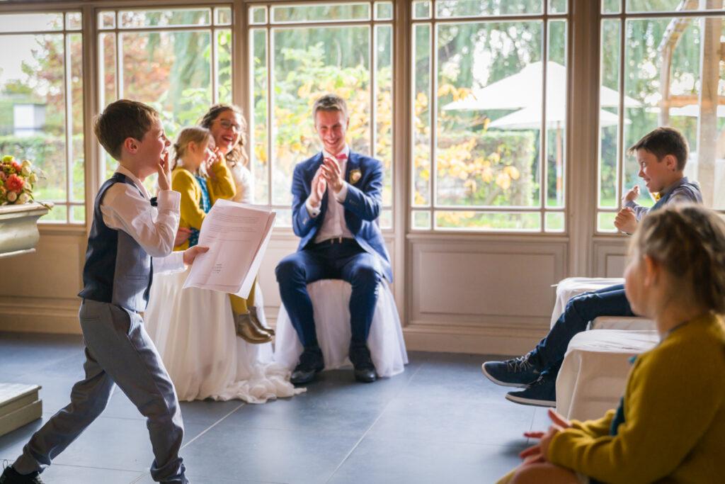 Bruidspaar kijkend naar speech van neefje tijdens huwelijksceremonie. Huwelijksfotografie in reportagestijl.