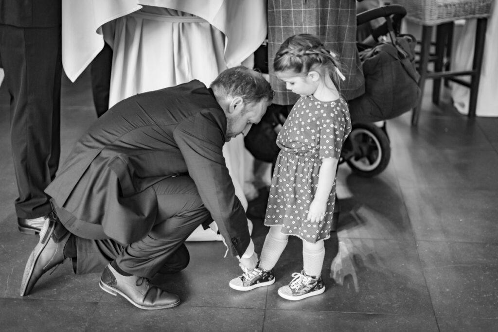 Papa die schoenveter opnieuw knoopt van zijn dochter op de huwelijksreceptie. Huwelijksfotografie in reportagestijl