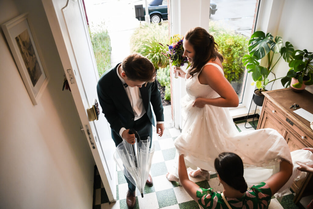 Eerste ontmoeting bruid en bruidegom op huwelijksdag in de hal. Huwelijksfotografie in reportagestijl
