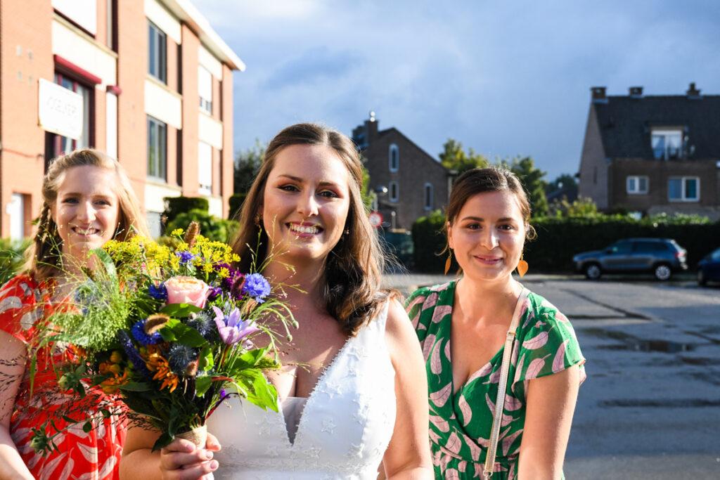 Bruid glimlachend met twee getuigen voor de auto. Huwelijksfotografie in reportagestijl.