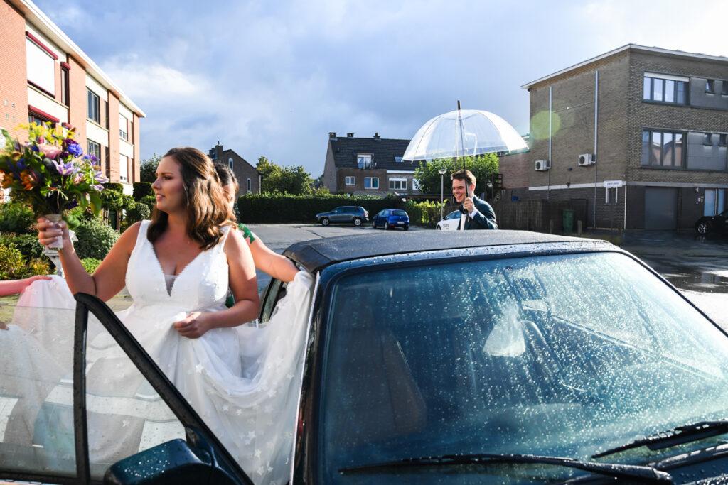 Bruidegom met paraplu op weg naar bruid voor de auto. Huwelijksfotografie in reportagestijl
