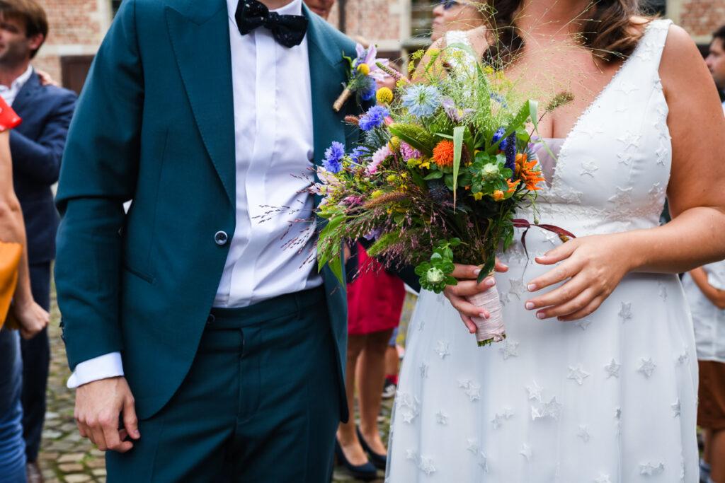 Bruid en bruidegom met huwelijksboekt zij aan zij wachtend voor gemeentehuis. Huwelijksfotografie in reportagestijl