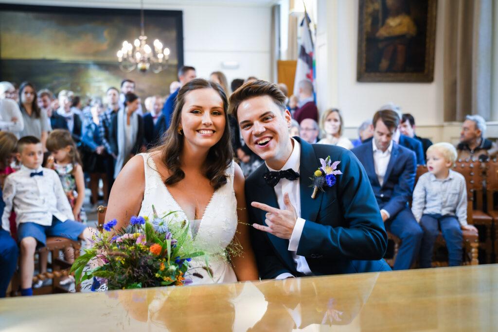 Koppel zittend in het gemeentehuis net voor huwelijksceremonie. Huwelijksfotografie in reportagestijl.