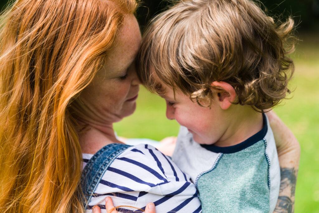 mama die haar zoon knuffelt buiten in het park. Familie en portretfotografie