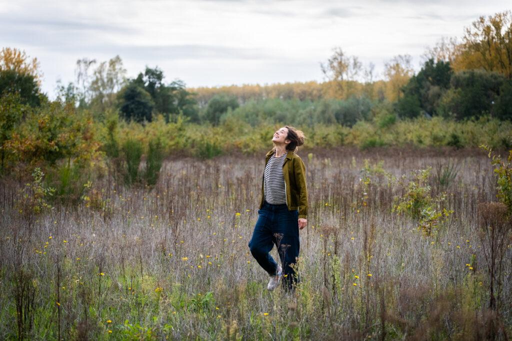 Vrouwelijk portret lopend door het gras met haar ogen dicht. Familie en portretfotografie