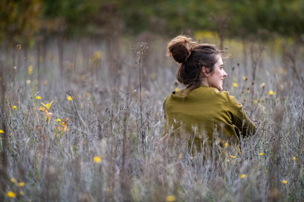 Vrouwelijk portret zittend in hoog gras met rug naar de lens. Familie en portretfotografie