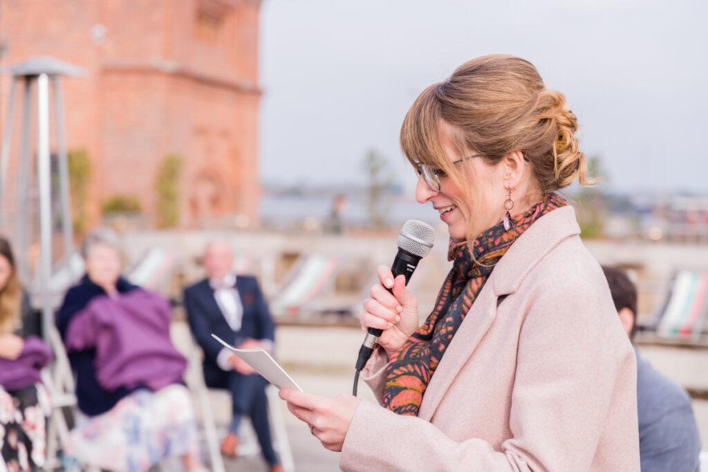Vrouwelijke ceremoniemeester sprekend op een huwelijk buiten. Familie en portretfotografie