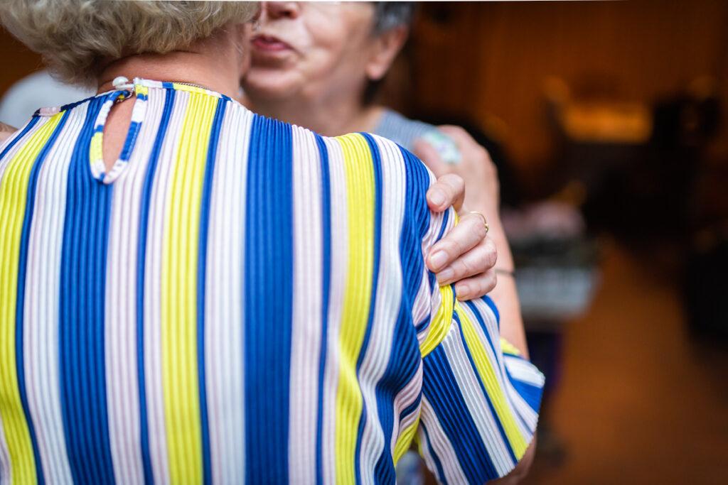Omhelzing en begroeting van twee vrouwen op een huwelijksverjaardag. Familie en portretfotografie
