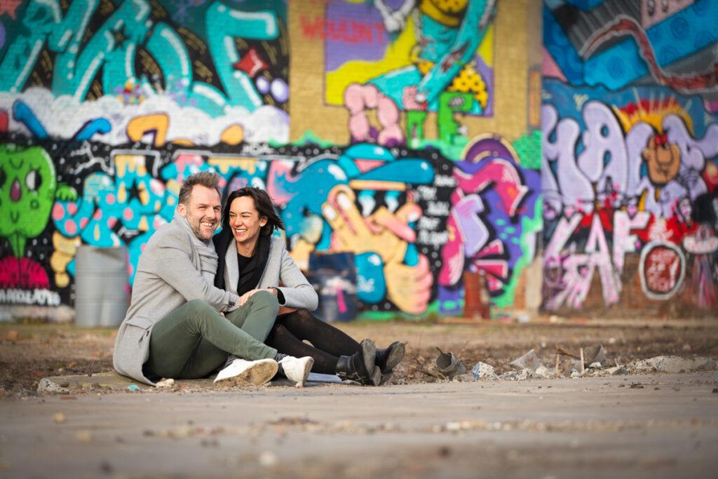 Verliefd koppel zittend op de grond voor een graffiti muur. Familie en portretfotografie