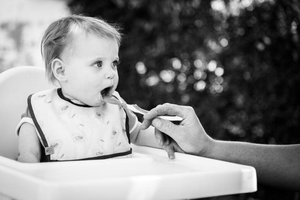 Kind in kinderstoel die eten krijgt. Familie en portretfotografie