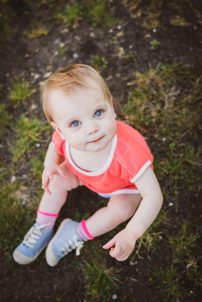 Baby meisje zittend in het gras in fel roos pakje. Familie en portretfotografie