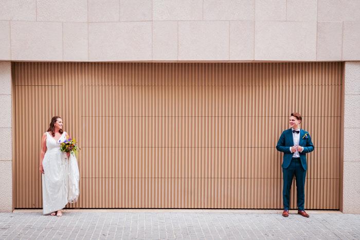 Bruid en bruidegom kijkend naar elkaar voor een beige architecturale muur. Huwelijksfotografie in reportagestijl