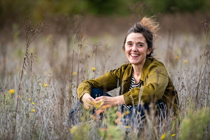 Vrouwelijk zittend portet in de natuur tussen de grassen. Portretfotografie