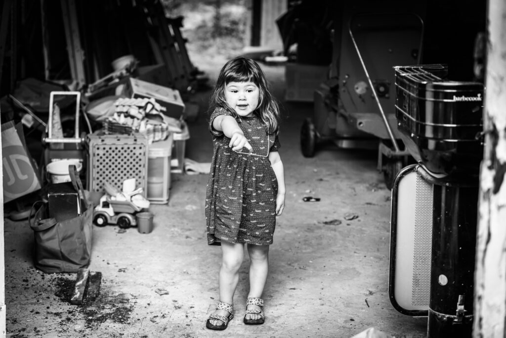 Kindje wijzend in hangar vol gerief zwart-wit. Familie en portretfotografie