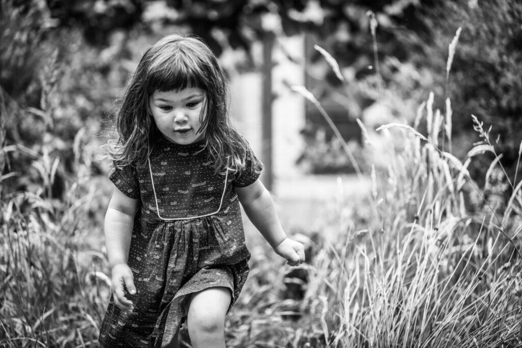 Meisje dat door het gras loopt in de natuur. Zwart-wit fotografie