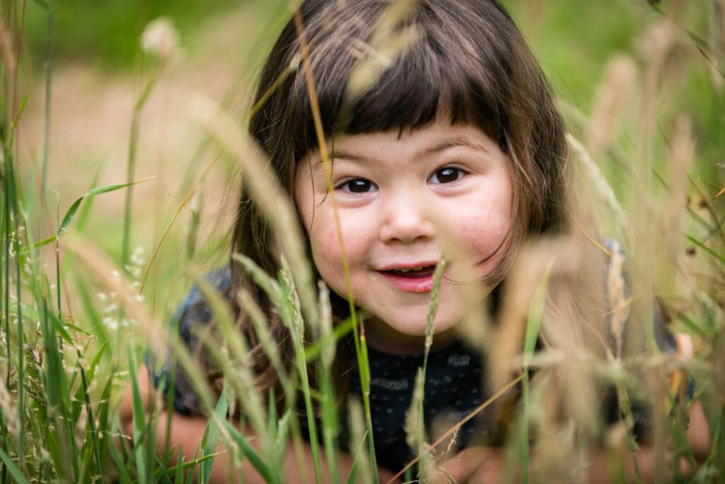 Kindje lachend kijkend in de lens tussen gras. Familie en portretfotografie