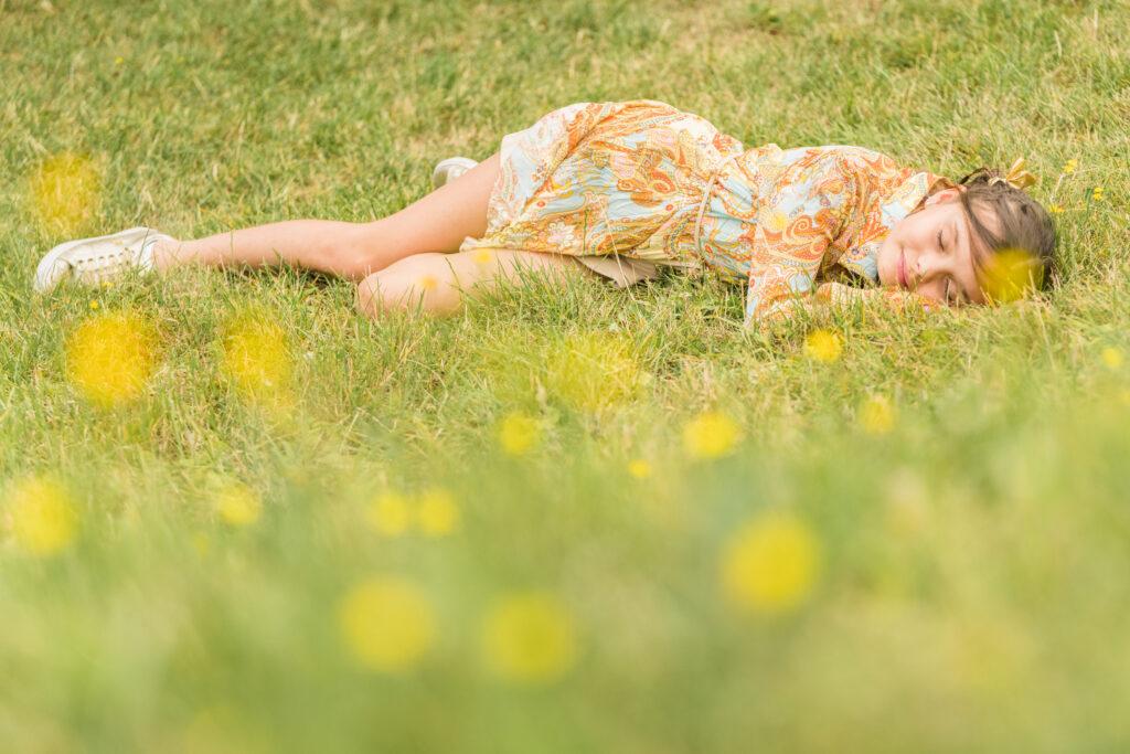 Meisje liggend op haar zij in het gras. Portret en familiefotografie