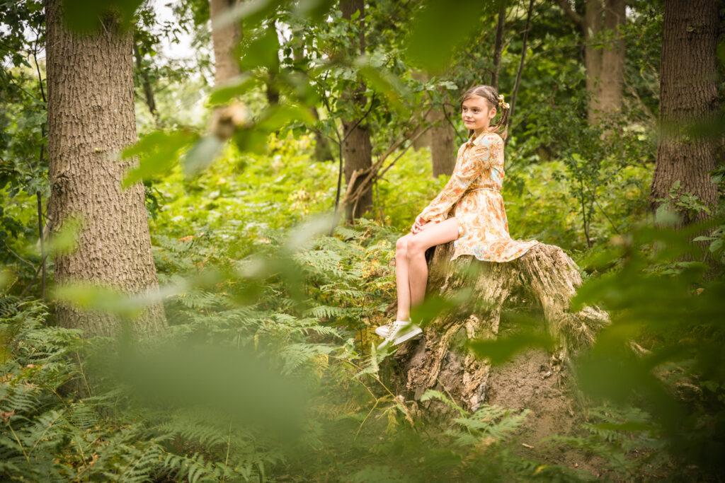 Meisje zitten op een boomstronk. Portret en familiefotografie