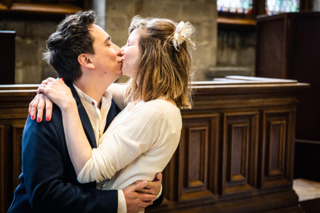 Koppel kussend in het gemeentehuis net na huwelijksceremonie. Huwelijksfotografie in reportagestijl.