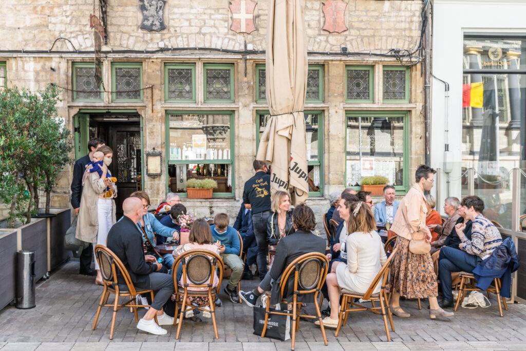 Receptie op café al zittend na de huwelijksceremonie in coronatijden. Huwelijksfotografie in reportagestijl.