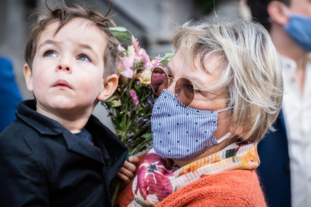 Zoontje van het bruidspaar kijkend naar de lucht, oma met mondmasker voor corona. Huwelijksfotografie in reportagestijl