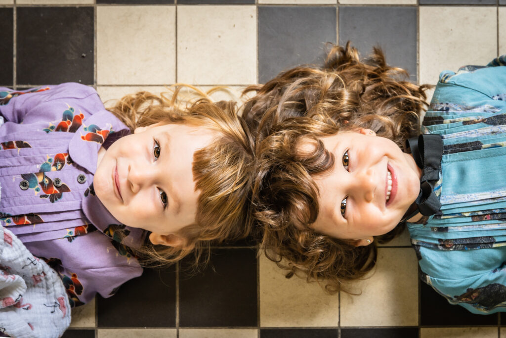 Twee zusjes liggend op de grond. Familie-en-portretfotografie-kinderfotografie