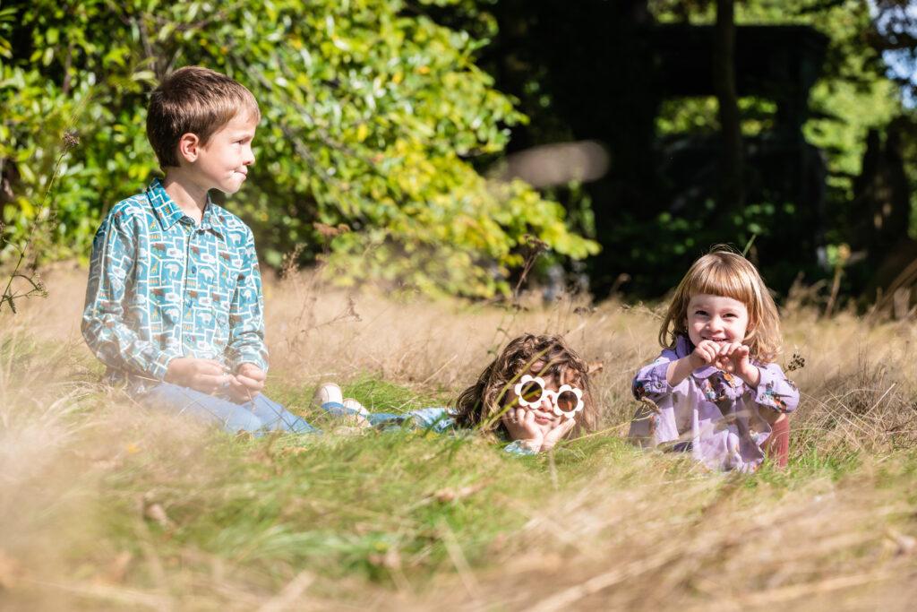 Broer met 2 zussen zitten in het gras. Familie-en-portretfotografie-kinderfotografie