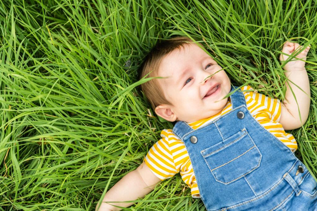 Lachend kindje liggen in hoog groen gras. Familie-en-portretfotografie-kinderfotografie