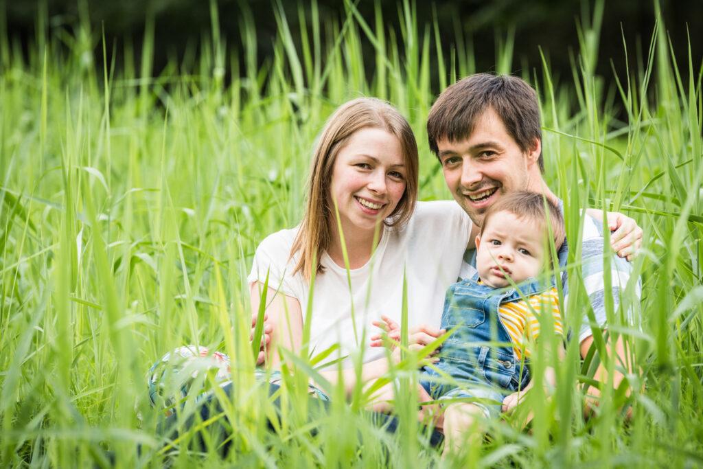 Familie zittend in hoog groen gras. Familie-en-portretfotografie-kinderfotografie_74