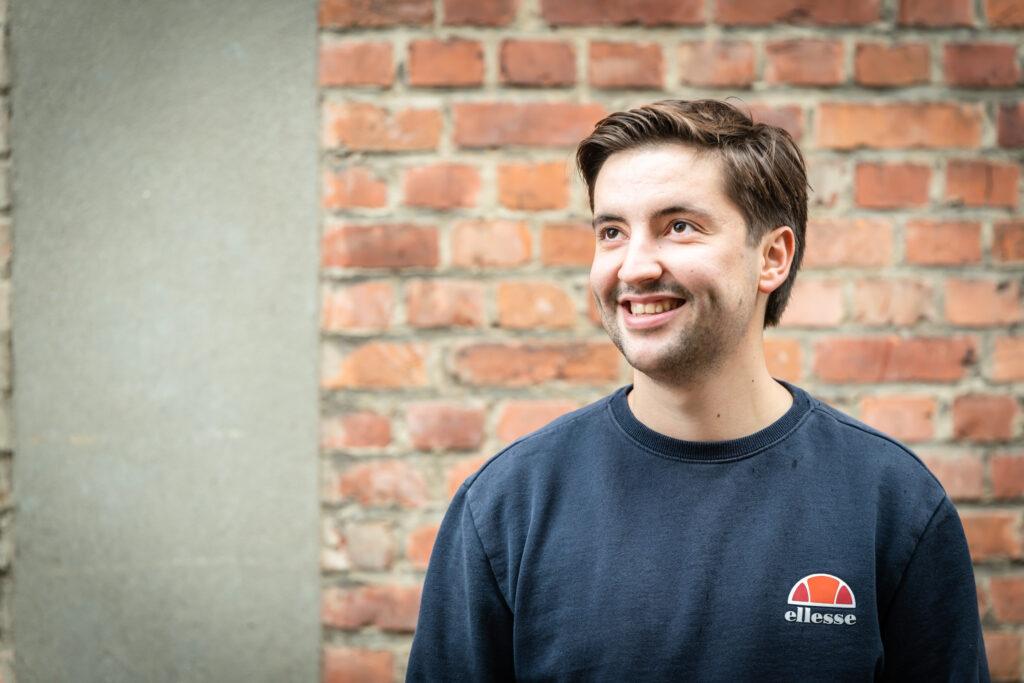 Portret van jonge man tegen bakstenen muur. Familie-en-portretfotografie